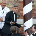 George Clooney gestures as he leaves by taxi boat to travel to the venue. (ALESSANDRO BIANCHI/REUTERS)