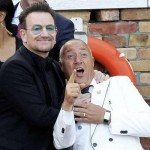 Irish singer Bono, lead vocalist of band U2, jokes with a hotel staff before boarding a taxi boat transporting guests to the venue. (ALESSANDRO BIANCHI/REUTERS)