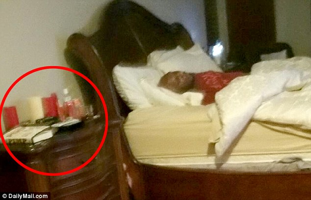 Accessories: On the bedside table, circled, are what appear to be a copy of Pimp, the autobiography of the brothel's owner, Dennis Hof; a black sex toy; candles; and baby oil. (Photo: Daily Mail)