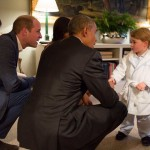 Prince George meeting President Barack Obama and First Lady Michelle Obama, wearing his royal bathrobe. (Photo: Release)