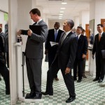 Obama surreptitiously tips the scales as White House trip director Marvin Nicholson weighs himself on a tour of a locker room at the University of Texas. (Photo: Archive)