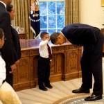 President Obama bends down to allow the son of a White House staff see if the president's haircut felt like his own. (Photo: Archive)