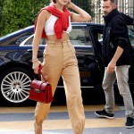 July 1—Out in Paris, wearing a red sweater, white crop top, high-waisted khaki trousers, red crocodile handbag, nude pumps and Versace sunglasses. (Photo: WENN)