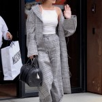 June 5—Wearing an oversized gray plaid trench and trousers, white tank top, white sneakers, and a black conductor hat while out in New York. (Photo: WENN)