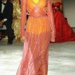 Kendall modeling a yellow body suit with a see-through pink wraparound dress on top at the 2017 Fashion for Relief catwalk. (Photo: WENN)