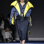 Kendall wearing a chick navy silk skirt, paired with a striking yellow and navy puffer jacket and pair of vibrant yellow sunglasses. (Photo: WENN)