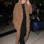 Rita wearing a casual comfy long brown fleece coat as she arrives to LAX. (Photo: WENN)