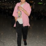 Rita arriving at Heathrow Airport wearing a bright pink jacket. (Photo: WENN)