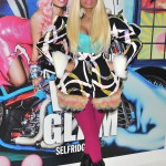 A blonde Nicki Minaj wearing a colorful coat standing in front of a pink haired Nicki Minaj with a matching latex dress. (Photo: WENN)