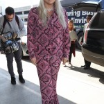 Kesha took it retro as she arrived at LAX airport in Los Angeles wearing a pink patterned long-sleeved, button-up top, with matching pants. (Photo: WENN)