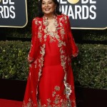 "Meher Tatna, the president of the Hollywood Foreign Press Association, donned a long-sleeve red dress with gold floral details. ""As part of her Indian culture, it's customary to wear a festive color during a celebration,"" a source told The Wrap. (Photo: WENN)"