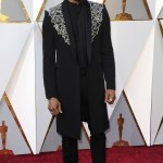 Chadwick Boseman wore a Givenchy look, which consisted of an elaborated silver embroidered long coat and shoes finished on top with matching silver zippers. (Photo: WENN)