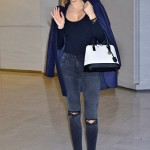 Kerr waved at the cameras as she arrived at the Tokyo International Airport in a ripped pair of dark jeans, matching booties, and a navy sweater and coat matching combo. (Photo: WENN)