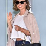 Miranda waved at the cameras as she arrived at Narita International Airport looking chic in a white crop top, blushed toned trench coat with white buttons and a big black handbag.