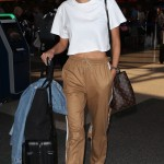 Alessandra arrived to L.A. showing a bit of her tummy in an oversized white cropped top, paired with camel tracksuit bottoms, and a matching Louis Vuitton bag. (Photo: WENN)