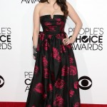 Kat Dennings co-hosted the 2014 People's Choice Awards rocking a black strapless cinched-waist dress with metallic rose print. (Photo: WENN)