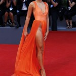 """Giulia Salemi went for a very revealing look at the Venice premiere of """"The Young Pope"""" in a bright orange dress with hip-high splits and plunging neckline. (Photo: WENN)"""