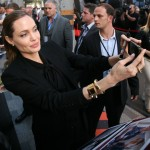 "The beautiful Angelina Jolie posing for a super rare selfie with a fan at the French premiere of her (former) husband's movie ""World War Z."" (Photo: WENN)"