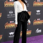 Zoe Saldana arrived solo at the Infinity War premiere wearing a plunging sleek white top paired with feminine black trousers by Givenchy with a large bow on the waist. (Photo: WENN)