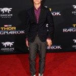 "The ""It"" actor attended the premiere of ""Thor: Ragnarok"" wearing a red and purple printed collar shirt underneath a navy striped jacket, grey trousers and white lace-up boots. (Photo: WENN)"