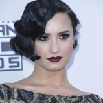 Demi Lovato perfectly balanced her 40's-inspired hair do with a deep vampy burgundy lipstick at the red carpet of the 2015 American Music Awards ceremony. (Photo: WENN)