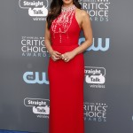 Munn hit the red carpet at the 2018 Critics' Choice Awards in a minimalist bright red halter-beck Prada dress featuring an array of jewels. (Photo: WENN)