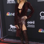 Jennifer Lopez stunned at the 2018 Billboard Music Awards in a daring head-to-toe burgundy crocodile ensemble by Roberto Cavalli styled with knee-high leather boots. (Photo: WENN)