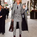 Lively wore three-piece suit by Ralph Lauren, consisting of a coat, suit jacket, and tailored pants, all in gray plaid, paired with a black tie and purple high-heeled combat boots. (Photo: WENN)