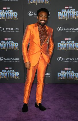 "Donald Glover attended the ""Black Panther"" premiere in a very orange Dolce & Gabbana suit with an even wilder printed shirt. (Photo: WENN)"