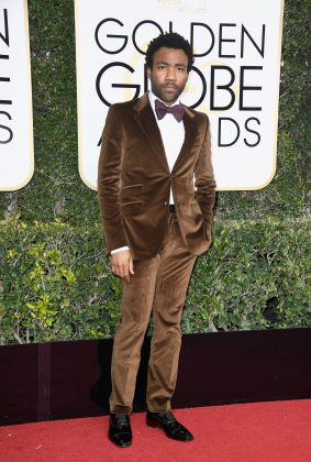 Donald Glover took the biggest style risk at the 2018 Golden Globes rocking a brown suede tuxedo that worked in his favor. (Photo: WENN)