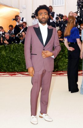 "Glover looked super cool while arriving at the 2018 Met Gala rocking a light purple Gucci tux featuring a diamond-encrusted ""Eye of Providence"". (Photo: WENN)"