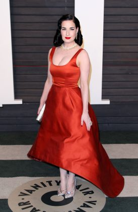 Von Teese stood out at the 2016 Vanity Fair Oscar Party in a high low satin dark orange ball gown designed by Zac Pose thatn accentuated her tiny waist. (Photo: WENN)