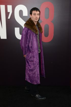 Ezra Miller pulled off a very fashionable bright purple fur coat on top of a casual stripped shirt and black pants while attending the New York City premiere of Ocean's 8. (Photo: WENN)
