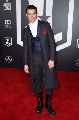 "Miller joined his ""Justice League"" peers at the premiere of their movie wearing a theatrical three-piece suit with high combat boots, a sating pocket square, and a glossy lip. (Photo: WENN)"