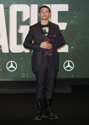 "The Flash posed at the photocall for ""Justice League"" waring a dark striped suit on top of a burgundy satin vest and a graphic tee, paired with black combat boots. (Photo: WENN)"