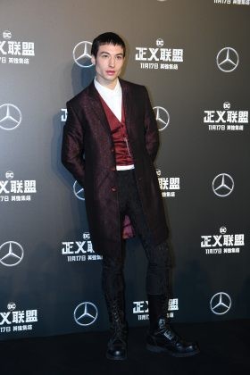 "Ezra Miller suited up for the Beijing premiere of ""Justice League"" a long burgundy printed blazer with matching sating vest and a crisp white button-up shirt. (Photo: WENN)"