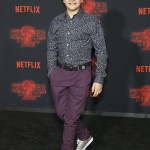 "The ""Stranger Things"" star attended the premiere of the show's second season rocking a pair of purple pants and a floral-print button-up navy shirt. (Photo: WENN)"