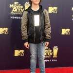 Gaten Matarazzo took the jeans-and-a-t-shirt casual look to the top with ultra-cool silky jacket black and green jacket at the 2018 MTV Movie and TV Awards. (Photo: WENN)