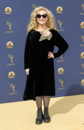 Carol Kane's black velvet dress with giant flower applique, dark sunnies, chunky boots and fishnet combo have her look a very costume feel. (Photo: WENN)