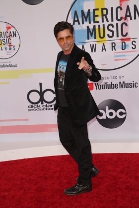John Stamos stepped out at the AMAs wearing the 2009 Jonas Brothers tour shirt as if that's a normal thing to do. (Photo: WENN)
