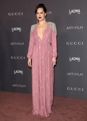 "The ""Fifty Shades"" star went glam in a pink plunging Gucci gown with statement shoulders covered in crystals as she walked down the red carpet of the 2017 LACMA Gala. (Photo: WENN)"