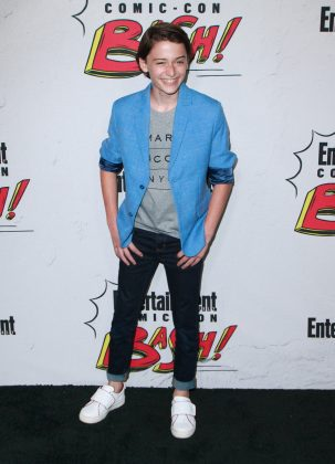 Noah Schnapp was all smiles at the 2017 EW Comic Con Party wearing a Marc Jacobs gray graphic tee underneath a stylish blue jacket with rolled up sleeves for a more casual look. (Photo: WENN)