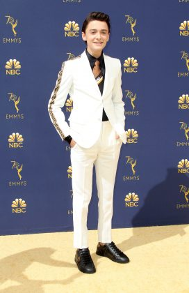 Noah Schnapp attended the 2018 Emmys in a white Fendi suit with brown logo stripe detailing down the sleeves, a matching taupe logo tie, all paired with a black button up. (Photo: WENN)