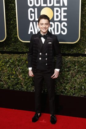 The young actor walked down the red carpet of the 2018 Golden Globes wearing a black crossed Balmain tux with and an Elizabetta Boutique scarf with a Times Up pin attached. (Photo: WENN)