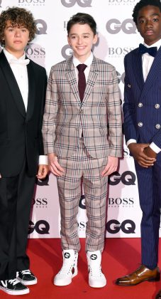 "Noah joined his ""Stranger Things"" friends at GQ'S 2017 Men of the Year wearing a gray plaid Ami suit, burgundy tie on top of a white shirt, and a pair of high-top Gucci sneakers. (Photo: WENN)"