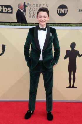 "The ""Stranger Things"" star stood out at the 2018 SAG Awards in an unexpected dark green custom tuxedo by Stella McCartney with velvety texture and black suede slippers. (Photo: WENN)"