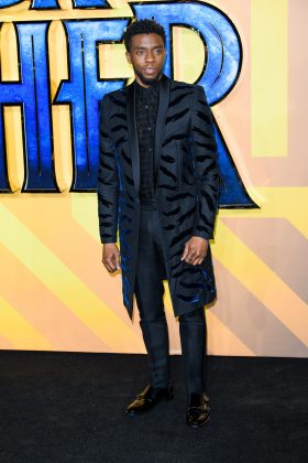 "King T'Challa celebrated African culture at his Marvel movie's London premiere in a long black coat with animal print pattern that brought his ""Black Panther"" vibes to life. (Photo: WENN)"