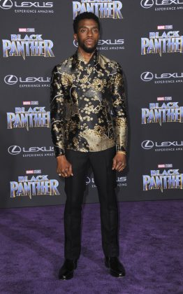 "Boseman rocked up at the Los Angeles ""Black Panther"" premiere in a silk dress shirt, intricately patterned with gold accents and paired with a pair of sharply tailored trousers. (Photo: WENN)"