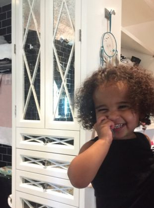 Sporting a full head of dark ringlet-style curls, Dream Kardashian crinkled her eyes at the camera while she hold her hand up to her face and grinned. (Photo: Instagram)