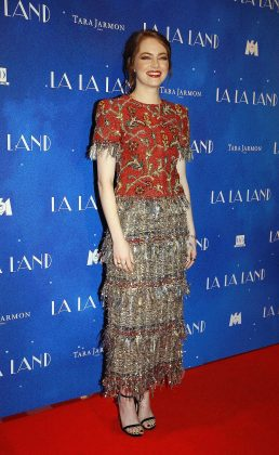 """Emma wore a red and gold patterned gown by Channel for the """"La la land"""" Paris premiere. (Photo: WENN)"""